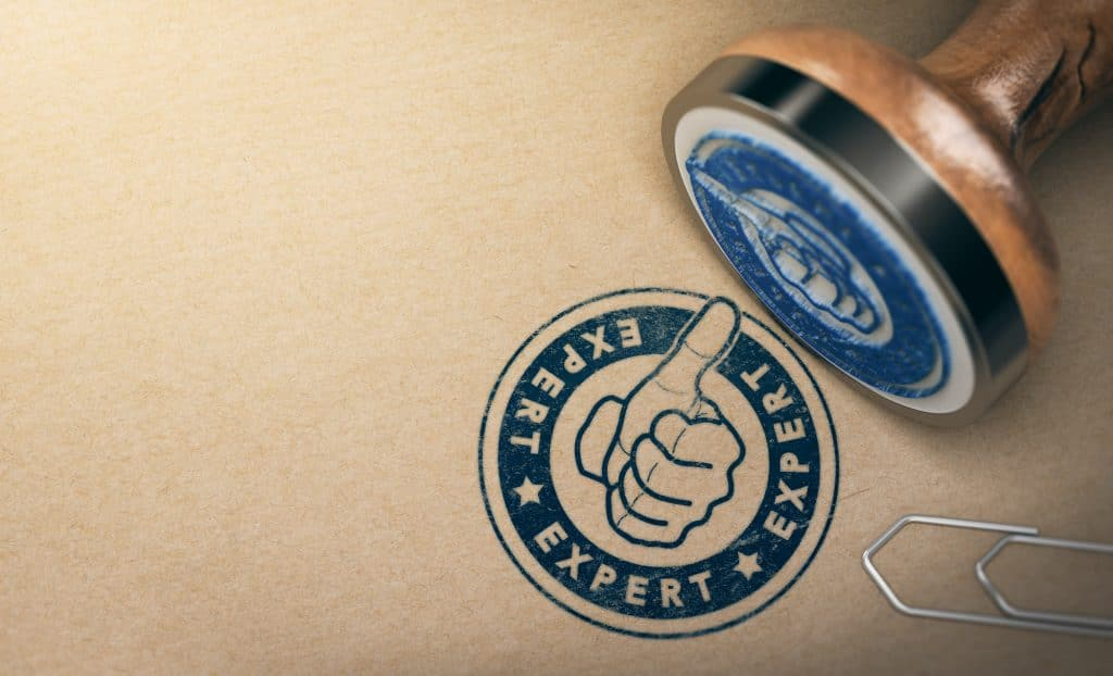 wooden Rubber Stamp over brown cardboard background with the text expert printed in blue color. Concept of certified radiology coding