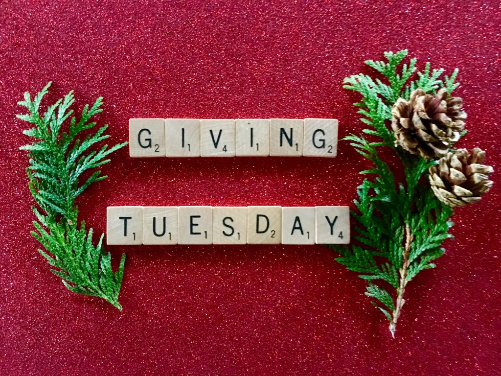 scrabble tiles that spell out givingtuesday surrounded by pine branches and pinecones