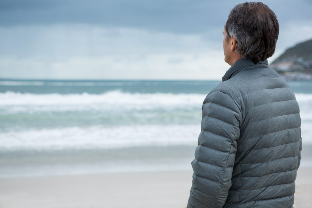 thoughtful man standing on beach with winter jacket on, winter wellness