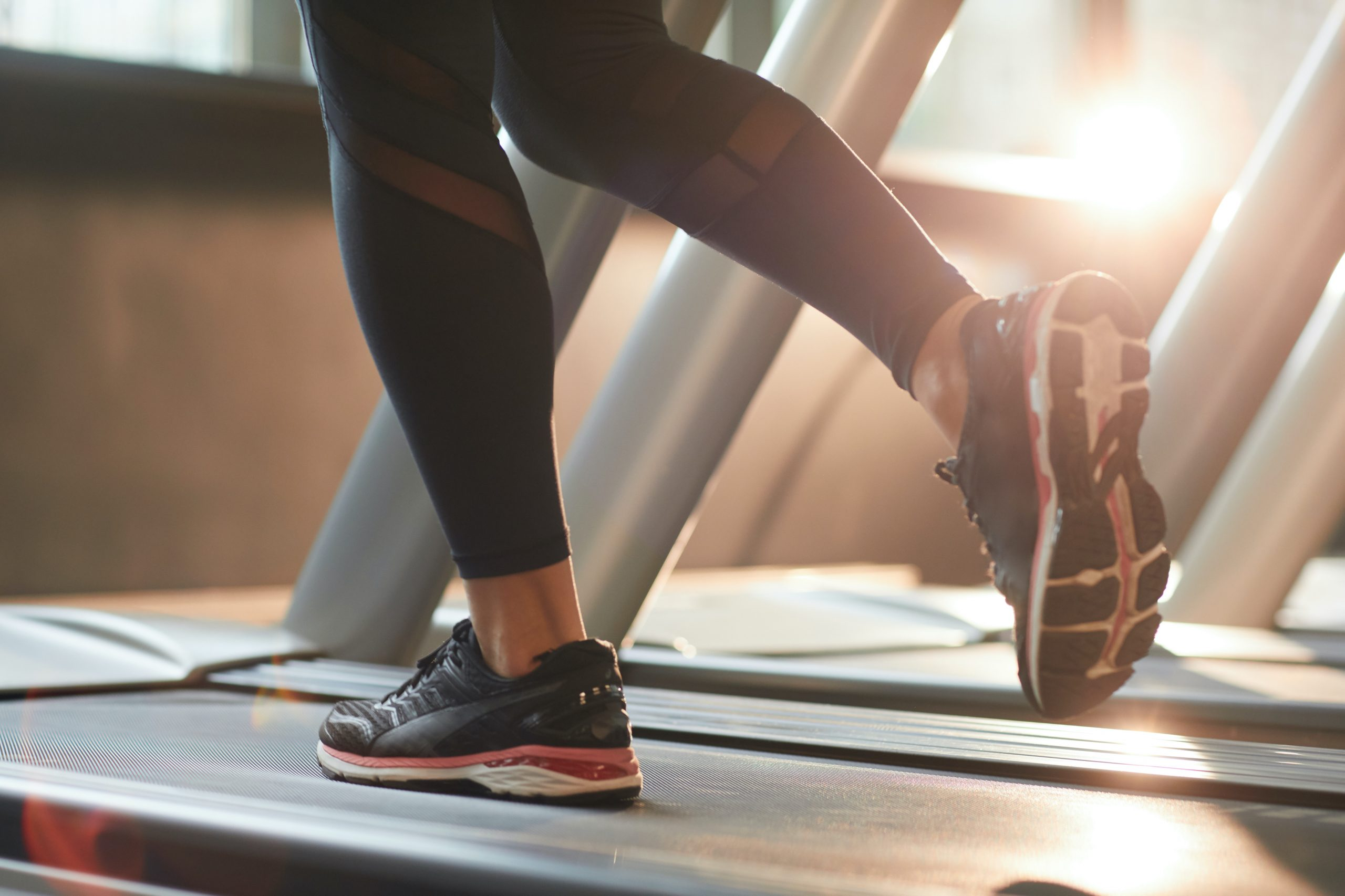 woman reducing stress by running on treadmill as part of a corporate wellness program