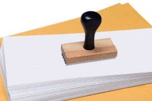 Envelopes and rubber stamp representing denials management