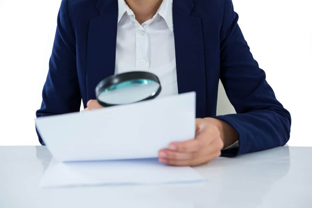 Mid section of businesswoman looking at document through magnifying glass, MIPS