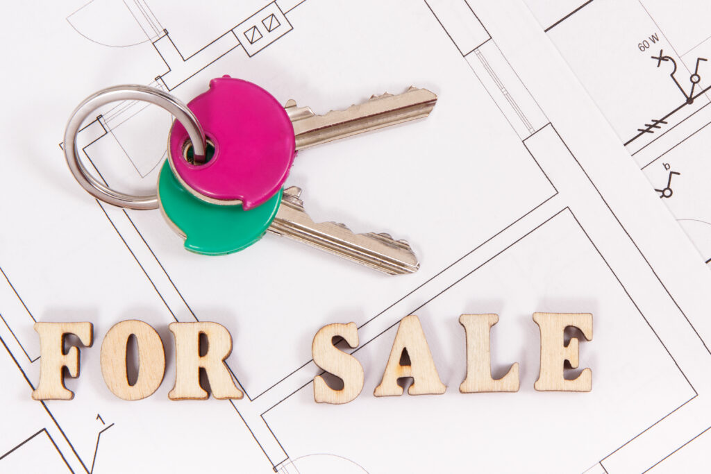 keys on top of medical practice blue print, buy or sell concept