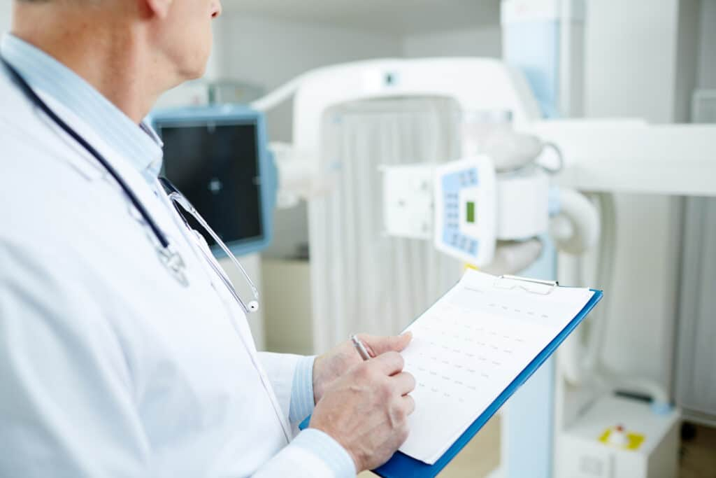doctor filling out anesthesia record for medical billing in patient chart