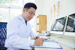 doctor sitting at desk doing paperwork, outsourced medical billing concept