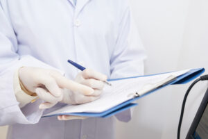 doctor filling out paper anesthesia record in patient's chart