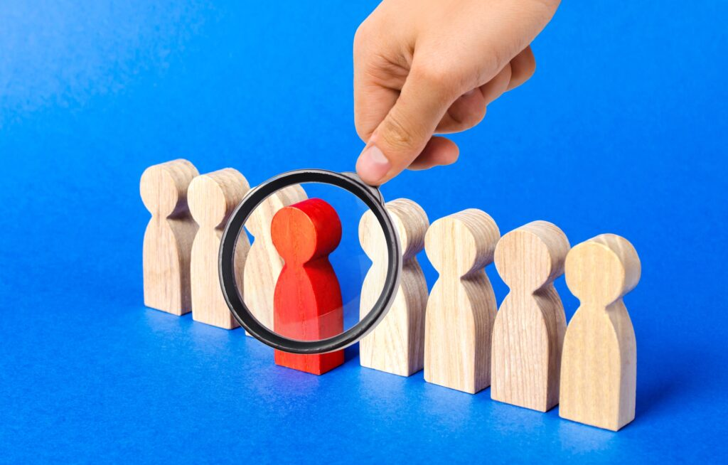 A magnifying glass looks at a red figure person in front of line of people. Leadership in healthcare.