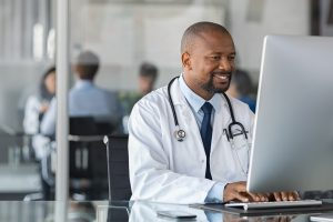 doctor at computer completing provider relief fund report
