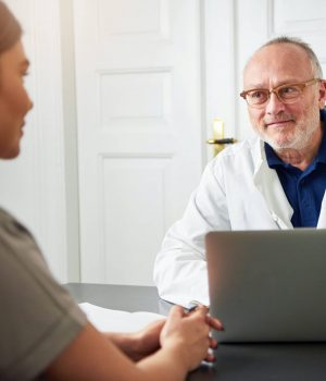 Senior doctor talking to young woman in clinic about patient satisfaction